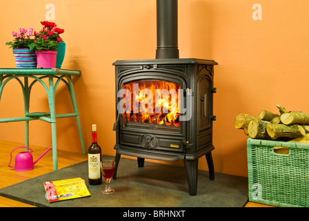 A Franco Belge wood burning stove in a cosy interior with bottle of red wine - Stock Photo