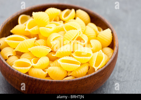 Uncooked Conchiglie pasta shells in a wooden bowl - Stock Photo