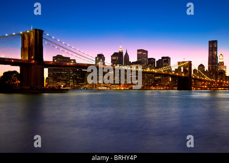 Dusk at the Brooklyn Bridge - spanning the East River connecting Brooklyn and Manhattan, New York City USA - Stock Photo