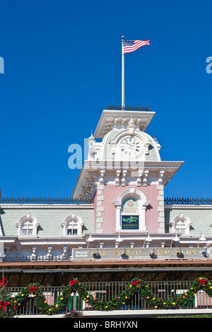 American flag flies over the railroad station near the entrance to the Magic Kingdom which is decorated for Christmas - Stock Photo