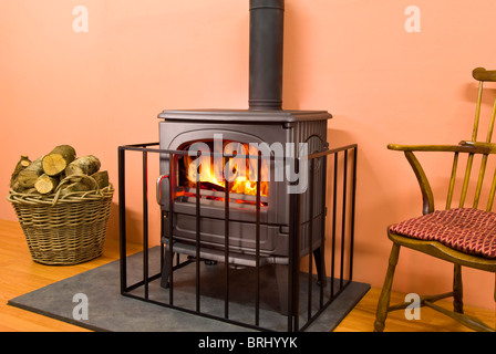 A Fire guard in front of a wood burning stove - Stock Photo