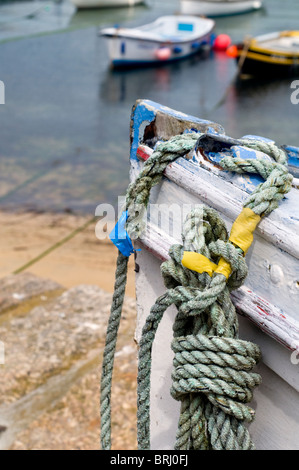 Boats in the harbour at Mousehole in Cornwall, England, UK - Stock Photo
