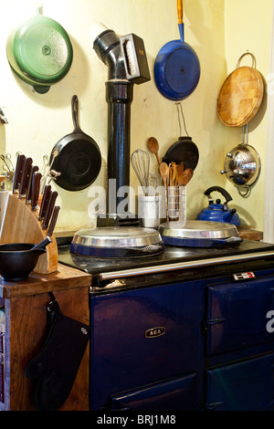 A corner of an English country style kitchen with an Aga or range and pots and pans and cooking utensils - Stock Photo