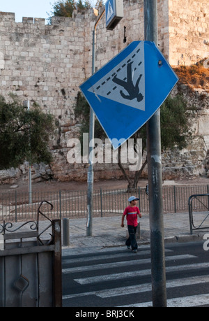 Israel. East Jerusalem. near Damascus gate. Boy crossing road at zebra crossing with city walls in bkgd - Stock Photo