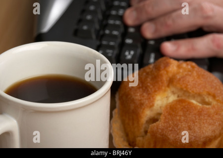 cup of black coffee and a muffin in front of a mans hand typing on a computer keyboard - Stock Photo