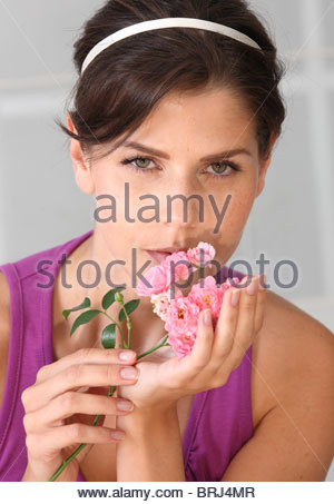 portrait of brunette woman with roses in hands - Stock Photo