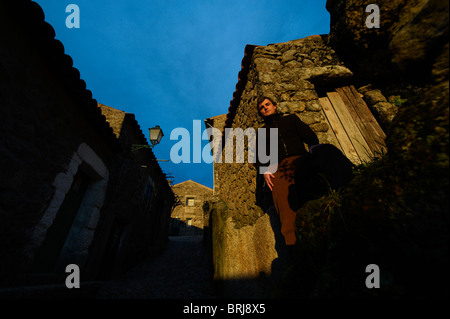 Man in front of traditional stone houses in the village of Monsanto, Portugal - Stock Photo