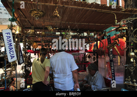 Back view of young man and woman looking at a market stall selling brass and copper ware, San Telmo Sunday Market, - Stock Photo