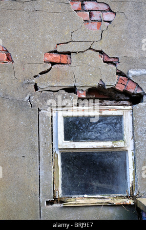 Decaying cement rendered brick wall and window - Stock Photo