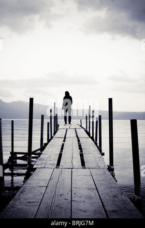 Girl standing at the end of a pier on lake looking outwards. - Stock Photo