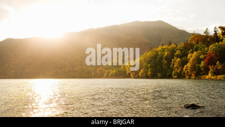 Lake Shikotsu in Autumn/Fall with sun directly in front. - Stock Photo