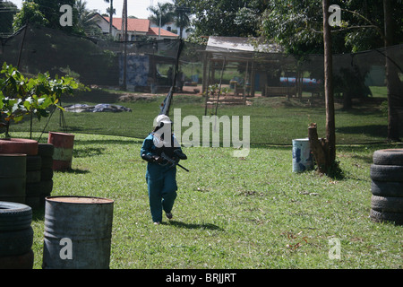 A young lady participating in a paintball game - Stock Photo