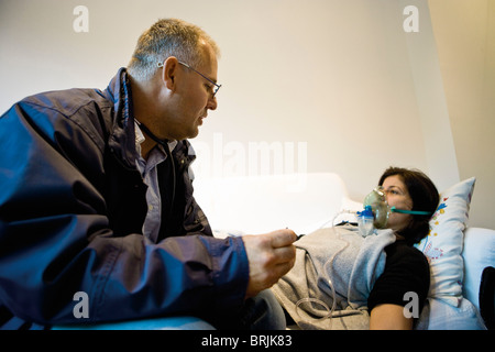 Emergency on-call doctor administering oxygen to patient in home - Stock Photo