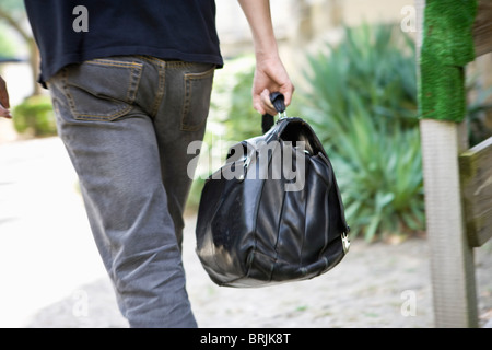 Man carrying bag, rear view - Stock Photo