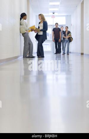 High school students talking in school corridor - Stock Photo