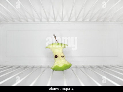 Single apple core sitting on shelf inside refrigerator - Stock Photo