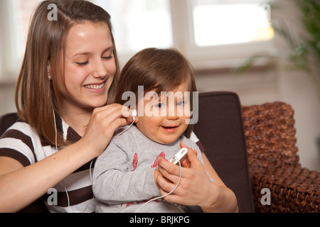 Teenage Girl with Baby Boy Listening to MP3 Player - Stock Photo