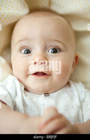 Infant looking at camera with wide eyes, portrait - Stock Photo