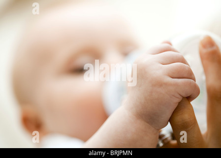 Baby drinking from bottle and holding mother's finger, close-up - Stock Photo