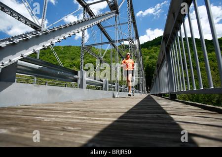 Woman runs across a steel bridge. - Stock Photo