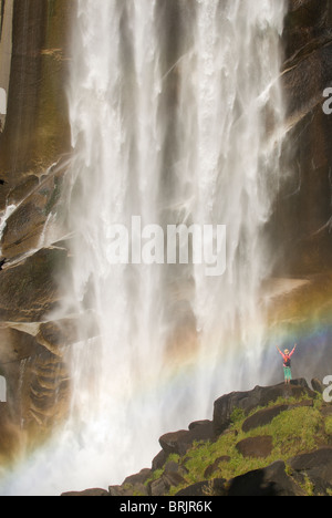 A young woman celebrates under a giant waterfall. - Stock Photo
