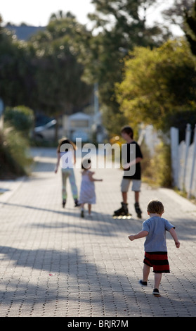 A group of kids are roller blading and walking down an alley. - Stock Photo