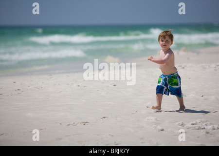 A little boy struts down the beach with the ocean in background. - Stock Photo