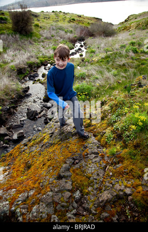 A young boy hiking along a stream. - Stock Photo