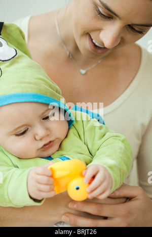 Mother and infant playing with rubber duck before bathtime - Stock Photo