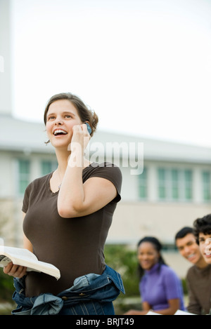 Young woman using cell phone, receiving good news - Stock Photo