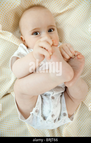 Baby touching its toes - Stock Photo