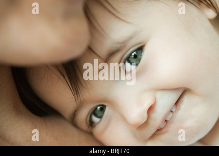Baby leaning against mother's chest, portrait - Stock Photo