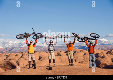 Four young men hold their bikes above their heads on the Slickrock Trail, Moab, UT. - Stock Photo