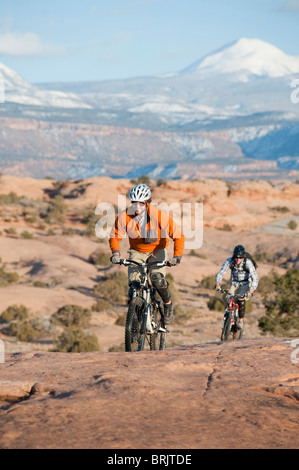 Two young men ride their mountain bikes on the Slickrock Trail, Moab, UT. - Stock Photo