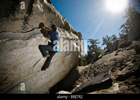 An Asian-American man rock climbs a boulder problem at The Tramway, Palm Springs, CA. - Stock Photo