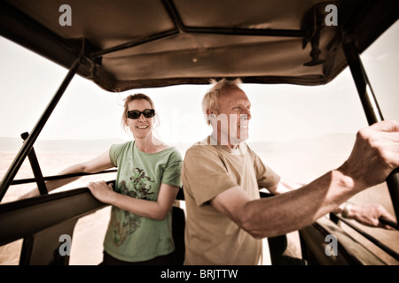 Father and daughter enjoy a wildlife safari in Ngorogoro Crater, Tanzania. - Stock Photo