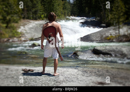 A young man stands with his guitar looking out on the river and nature. - Stock Photo