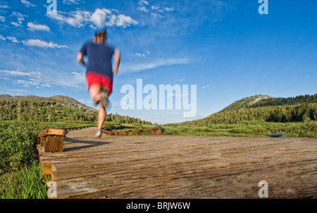 Heading out for an evening trail run, a young woman follows the wooden path to the trail in Lake Tahoe, Nevada. - Stock Photo