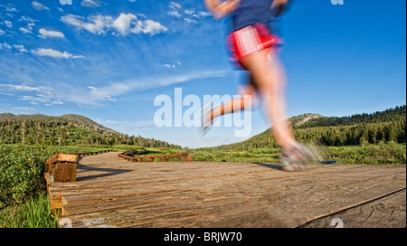 Heading in from an evening trail run, a young woman follows the wooden path back to the start in Lake Tahoe, Nevada. - Stock Photo