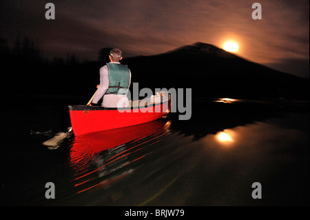 A man canoeing in a red boat at night on a mountain lake in Oregon. - Stock Photo