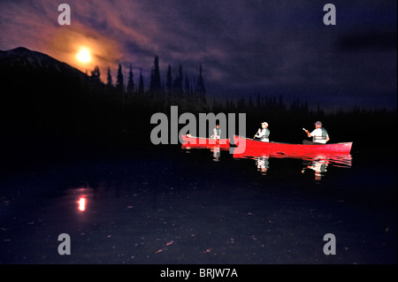 A group canoeing in a red boats at night on a mountain lake in Oregon. - Stock Photo