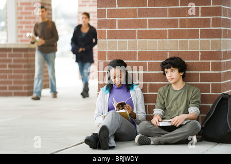 Students sitting together on sidewalk outside school - Stock Photo