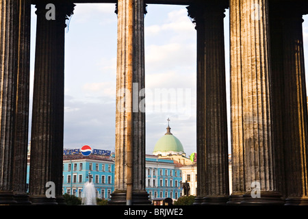 Pepsi sign and green dome of Catholic Church on Nevsky Prospect through the columns of  Kazan Cathedral St Petersburg - Stock Photo
