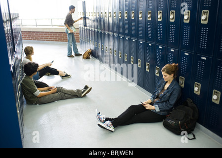 High school students sitting on floor by lockers using cell phones - Stock Photo