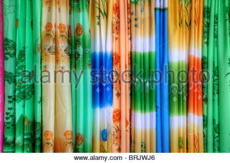Silk fabrics being sold in a Tibetan marketplace. - Stock Photo