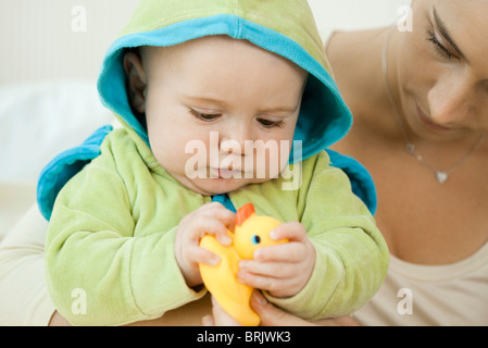 Baby playing with rubber duck before bathtime - Stock Photo