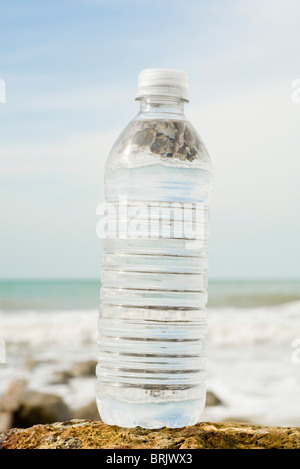 Bottle of water on shore - Stock Photo