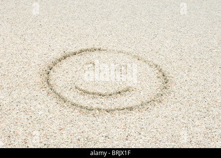 Smiley face drawn in sand at the beach - Stock Photo