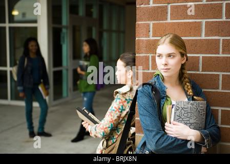 High school students waiting outside school - Stock Photo