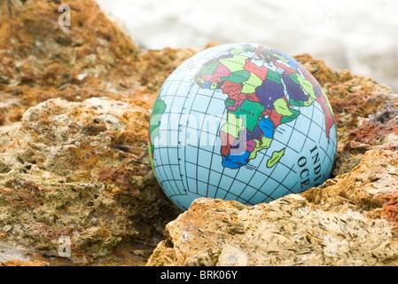 Globe nestled in rock - Stock Photo